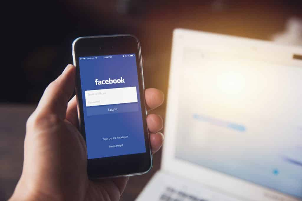 hand holding cell phone with the Facebook login screen on it